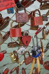 Love padlocks with heart shape.  Concept of love. Metallic  love padlock on a bridge full of padlocks.