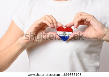 Love Paraguay. The girl holds a heart in the form of the flag of Paraguay on her chest. Paraguayan patriotism concept Stockfoto ©