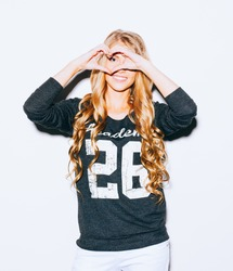 Love. Portrait smiling happy young woman with long blond hair, making heart sign, symbol with hands white wall background. Positive human emotion expression feeling life perception