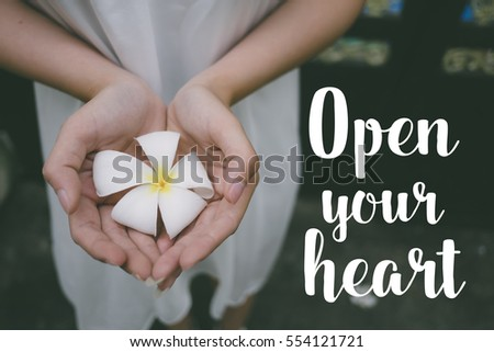 Love quote. Inspirational quote on the girl holding white flower. Open your heart. #554121721