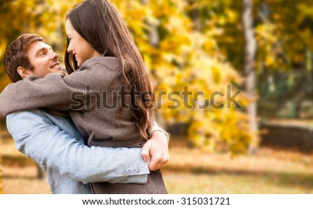 love, relationship, family, season and people concept - smiling couple hugging over autumn natural background