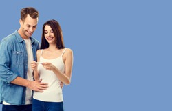 Love, relationship, new parents and happy family concept - young lovely couple, finding out results of a pregnancy test. Blue color background.