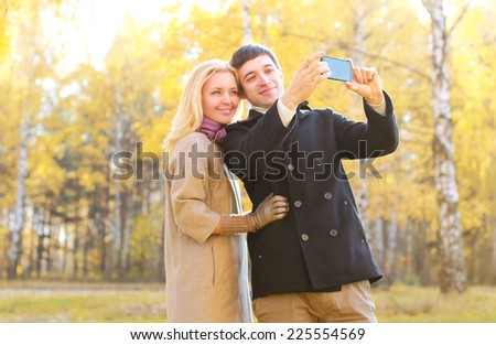 Love, relationship, season, technology and people concept - happy smiling couple in love making selfie in autumn park