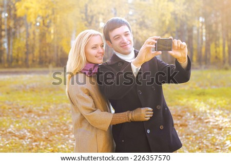 Love, relationship, technology and people concept - happy smiling couple in love making selfie outdoors in autumn park