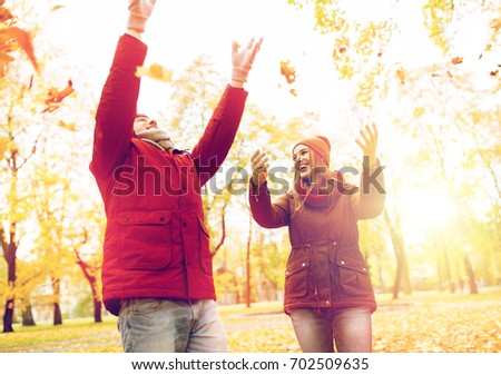 love, relationships, season and people concept - happy young couple throwing autumn leaves up in park #702509635