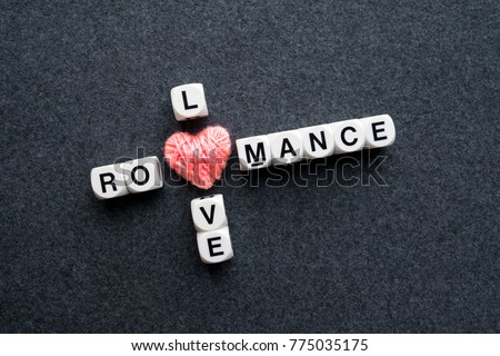 Love romance crossword block text with pink thread heart on dark felt background. Close up conceptual scrabble letter tiles forming love romance crossword