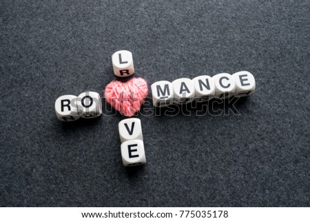 Love romance crossword block text with pink thread heart on dark felt background. Close up conceptual scrabble letter tiles forming love romance crossword  #775035178