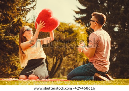 Love romance dating relationship leisure concept. Couple playing games in park. Girl and her man passing heart spending time on picnic.
