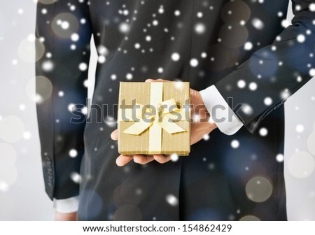love, romance, holiday, celebration concept - man hiding gift box