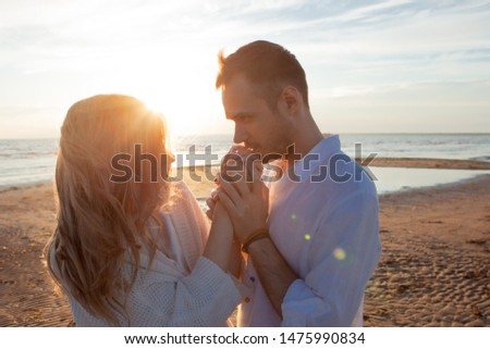 Love, romance, tenderness. A young couple sensually holding hands. The wind waves the girl's hair. Close-up, dynamic photo.