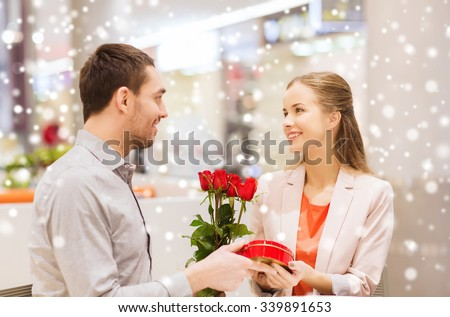 love, romance, valentines day, couple and people concept - happy young man giving red roses and present to smiling woman at cafe in mall with snow effect