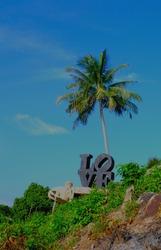 Love sculpture under a palm tree on an island