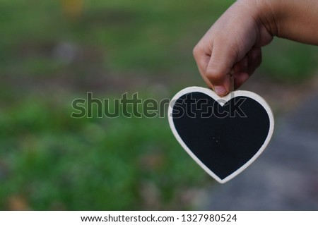 Love shape blackboard with child hand. Selectively focused.  #1327980524