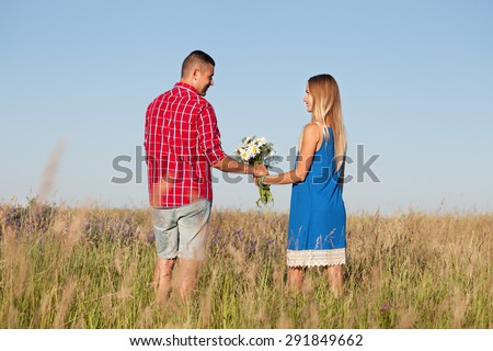 Love story. Beautiful young couple walking in meadow, outdoor. Portrait of stylish fashion man and woman posing in summer in field. Series. Back view