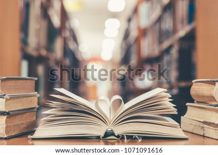 Love story book with open page of literature in heart shape and stack piles of textbooks on reading desk in library, school study room for national library lovers month  and education learning concept