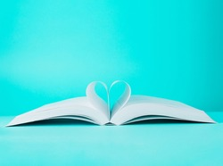 Love story book with open page of literature in heart shape on turquoise blue background. World Book Day, Teachers Knowledge. Minimal composition with copy space.