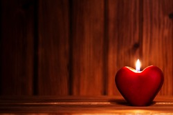 Love story concept. Close-up view of red burning candle in the shape of heart on old wooden background with place for your text. Focus on the candle