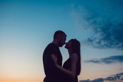 Love story . Couple at sunset. On the background of the sky. Clouds.