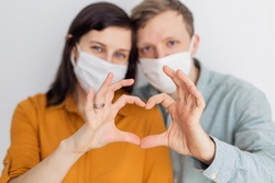 Love story family husband wife boyfriend girlfriend quarantined. Normal life with coronavirus. Lifestyle COVID-19. Quarantine virus protection sterility  home together  heart symbol