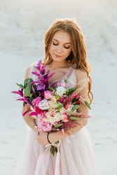 Love Story of a beautiful couple in a pink wedding luxury dress with a bouquet in the Sahara desert, sand, dunes