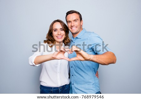 Love story of cheerful, attractive, mature, adult, lovely, cute, sweet couple in casual outfit, jeans, shirt making heart with fingers over grey background #768979546