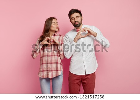 Love symbol. Affectionate romantic woman and man keep lips folded, make heart gesture, express good feelings, wear shirt and trousers, want to kiss each other, isolated over pink background.