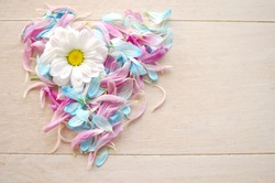 Love symbol on wooden background maid by blue and pink petals with daisy flower.