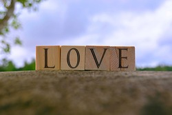 Love text on wooden block on top of big stone with blue sky background