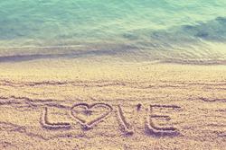 Love text wrote  on beach sand