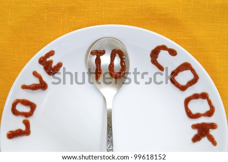 love to cook written by tomato sauce on white plate and silver spoon
