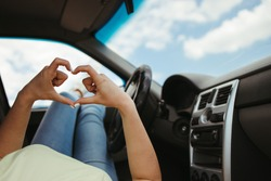 Love to travel. Young woman showing heart sign with her arms resting while car traveling. Road trip, friendship and travel concept