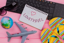 Love travel on notebook with woman's traveler accessories glasses wallet and flip-flops on pink table top background. Globe black keyboard grey miniature airplane.