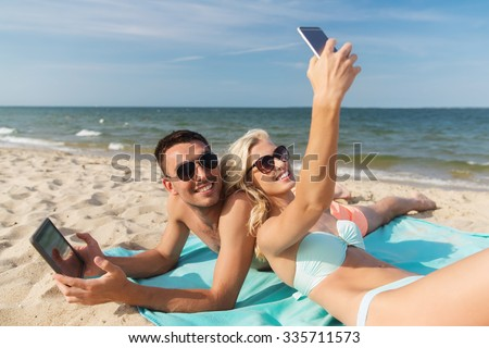 love, travel, tourism, technology and people concept - happy couple on vacation with tablet pc computer and smartphone sunbathing on summer beach #335711573
