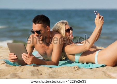 love, travel, tourism, technology and people concept - happy couple on vacation with tablet pc computer and smartphone sunbathing on summer beach #422962633