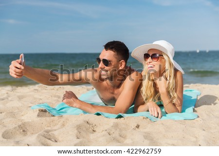 love, travel, tourism, technology and people concept - smiling couple on vacation in swimwear and sunglasses and taking selfie with smartphone on summer beach #422962759