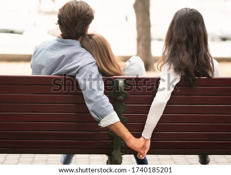 Love Triangle. Cheating Boyfriend Hugging Girlfriend Holding Hands With Her Girl Friend Sitting On Bench Together In Park Outdoor. Back-View Stock foto ©