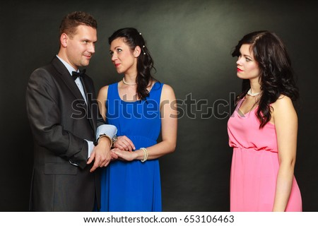 Love triangle concept. Man cheating on his wife, looking at other woman, choosing between two ladies. #653106463