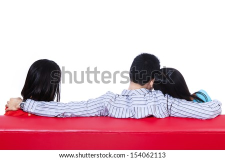 Love triangle of two woman and one man sitting on red sofa. Isolated on white