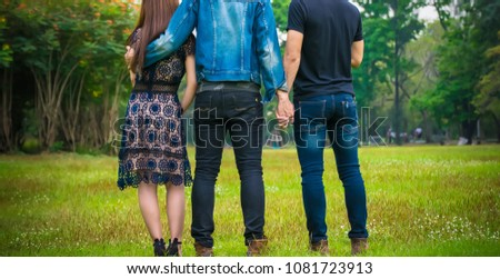 Love triangle. Young woman in relationship with two men.back view of threesome love friends of two men and one woman.