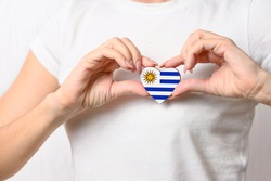 Love Uruguay. The girl holds a heart in the form of the flag of Uruguay on her chest. Uruguayan patriotism concept