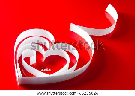 "Love valentine heart. White paper ribbon heart with letters ""Love"" inside on red"