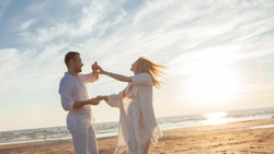 Love, waiting for the baby. Couple, pregnant woman and man, in white flying clothes, walk, hold hands, dance gainst the backdrop of the sunset sea, sandy beach and sky with clouds.