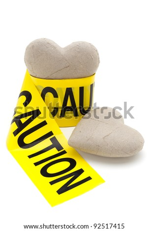 Love with caution sign, two paper hearts with yellow caution tape isolated on white background