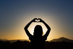 Love with hands. Funny girl silhouette at the sunset doing an heart with her hands. Concept about lifestyle, people, love and nature.