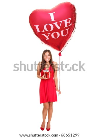 Love woman holding valentines day gift and heart balloon saying ?I love you?. Beautiful young woman smiling in red dress. Asian / Caucasian female model isolated on white background in full length.