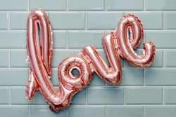 Love word from pink inflatable balloon on mint tile wall background. The concept of romance, Valentine's Day. Love rose gold foil balloon