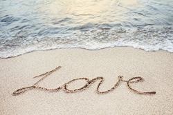 love word handwritten on a sandy tropical beach with soft ocean wave on background