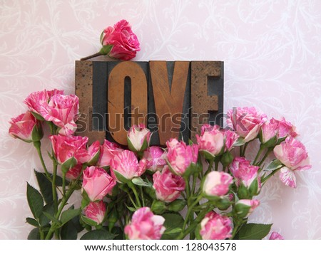 love word in wood type with fresh miniature roses