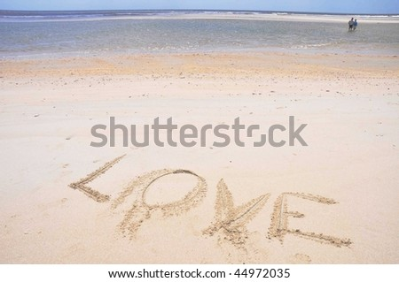 Love written in the sand by the ocean
