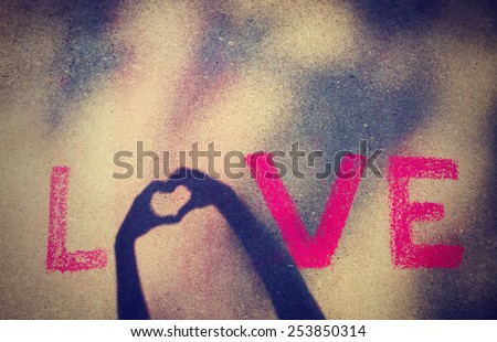 love written with chalk and then a shadow from two hands displays the O in the work with a heart with a instagram filter (shallow depth of field)